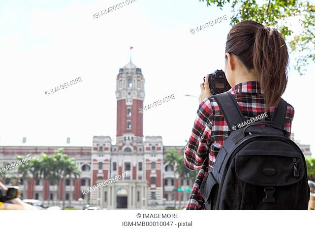 Young woman taking photos with rear view