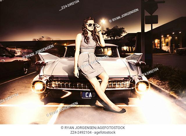 Creative dynamic vintage photograph of a retro pin-up from 1960s sitting on the back end of a classic old american muscle car in retro fashion