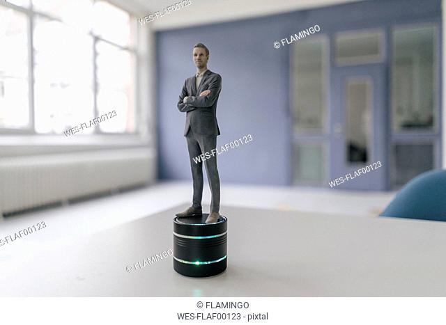 Miniature businessman figurine standing on smart home loudspeaker