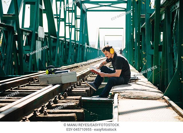 Young construction worker man rests sitting reading a book on an old steel railway bridge