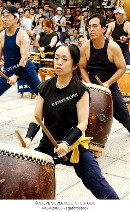 Women and men playing taiko drums during musical performance. Gion Matsuri (festival), Yasaka shrine, Kyoto, Japan