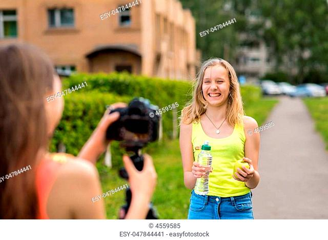 For the girl student. Writes video to the camera. In the hands holding an apple in a bottle of water. Write down a vlog and a blog about proper nutrition