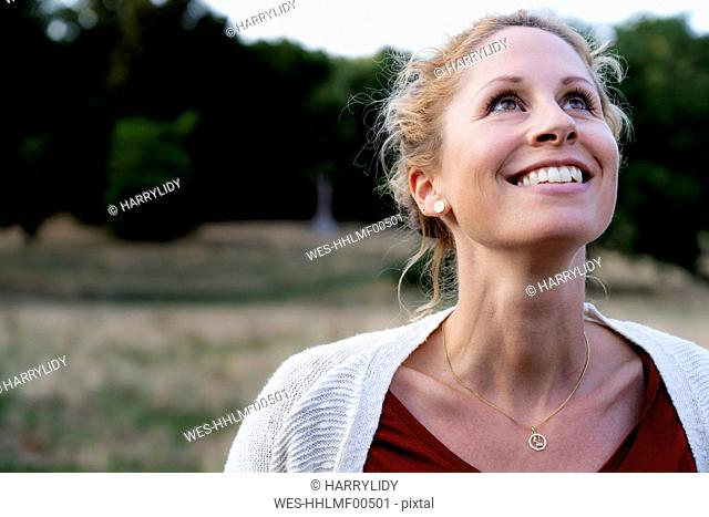 Portrait of smiling woman in nature looking up