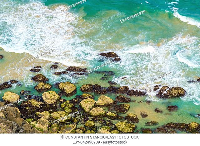 Aerial view over green turquoise water waves in Byron Bay, Australia. Nature background with ocean waters and rocks in sunny day