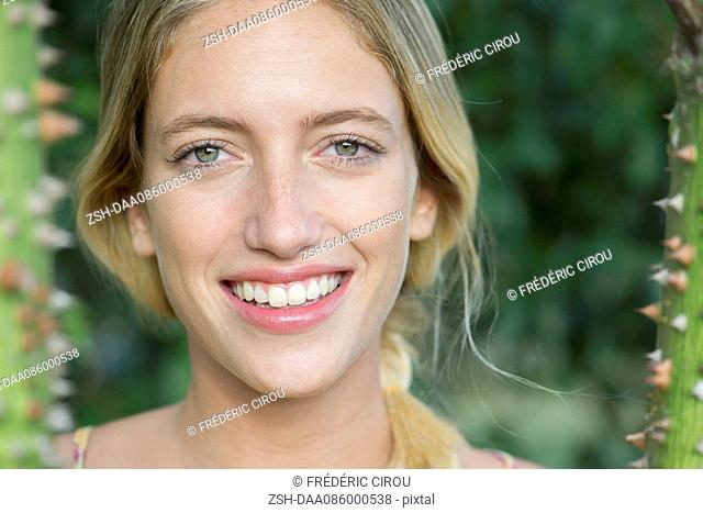 Young woman smiling cheerfully, portrait