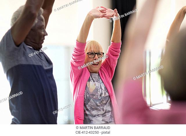 Smiling active seniors exercising, stretching arms