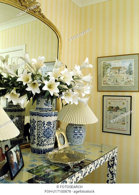 Close-up of lilies in blue+white vase on console table