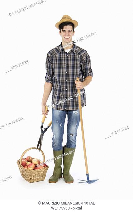 Young farmer with shears and rake, at his feet a basket full of red apples, he is wearing a straw hat, checked shirt and green rubber boots