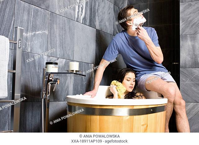 Couple in bathroom. Man shaving and woman having bath