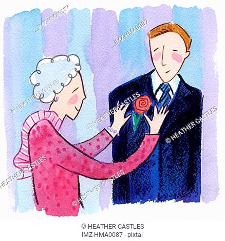 A grandmother pinning a boutonniere onto her grandsons suit