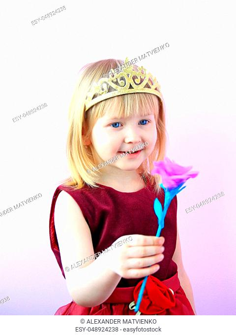 Little girl in crown giving flower. Little princess with pink flower. Cute girl with crown on head offering pink rose. Child in beautiful dress smiling