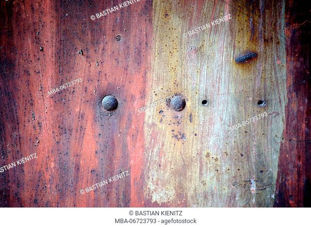 Close-up of a rusty metal surface with rust bubbles and rusted rivets