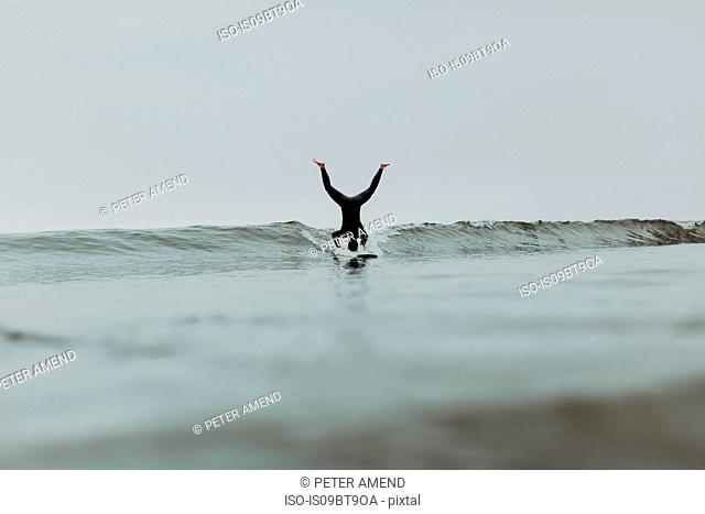 Young male surfer doing headstand on surfboard in misty sea, Ventura, California, USA
