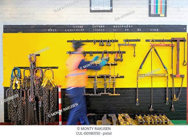 Engineer selecting lifting equipment in train engineering factory