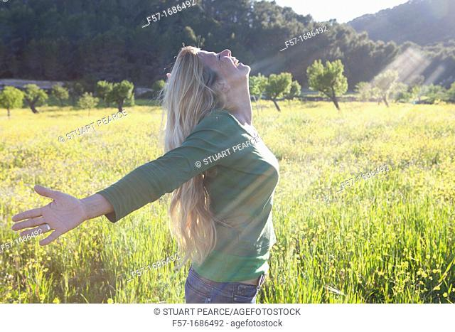 Forty something year old woman sun worshipping in a meadow