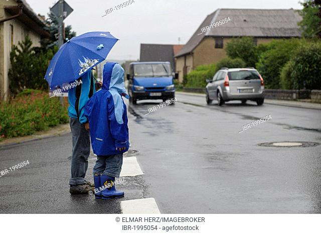 Two children, 4 and 8 years, waiting to cross the street in the rain, two cars, Assamstadt, Baden-Wuerttemberg, Germany, Europe