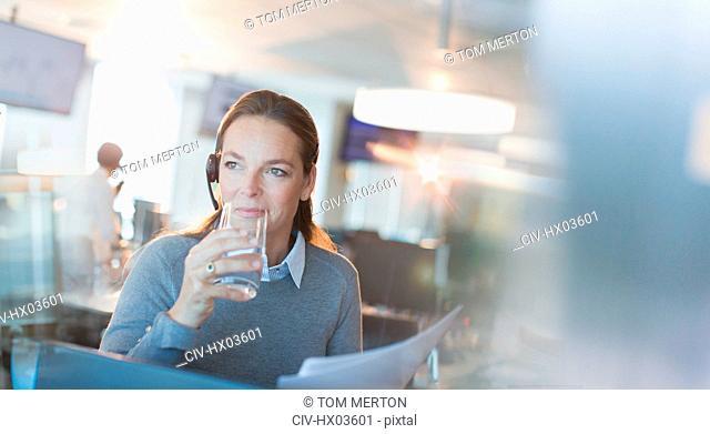Businesswoman wearing headset drinking water in office