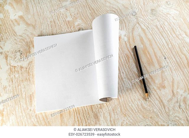 Blank opened brochure and pencil on light wooden background with soft shadows. Template for design presentations and portfolios. Top view