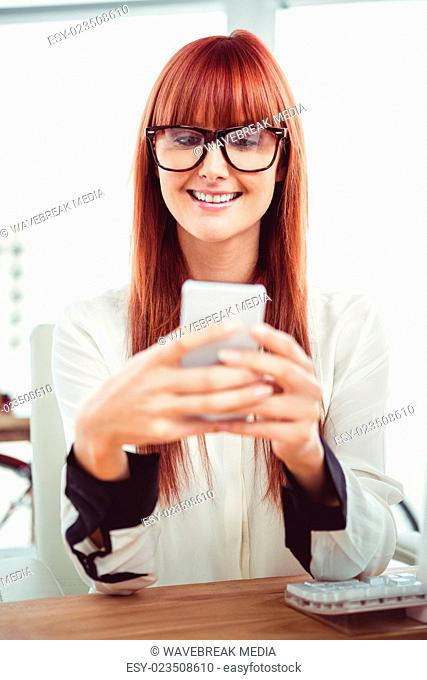 Smiling hipster businesswoman texting on her smartphone