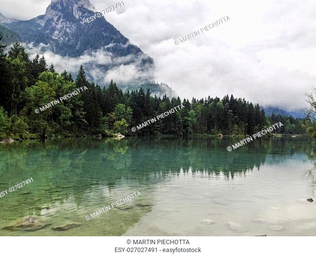 Mountain peaks shrouded in cloud and mist reflected in a calm lake surrounded by evergreen forests in Austria