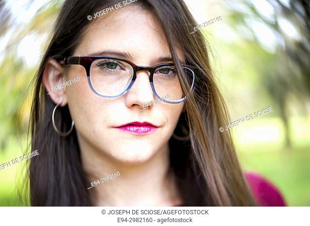 A casual portrait of a 26 year old woman with long brown hair and big glasses, outdoors