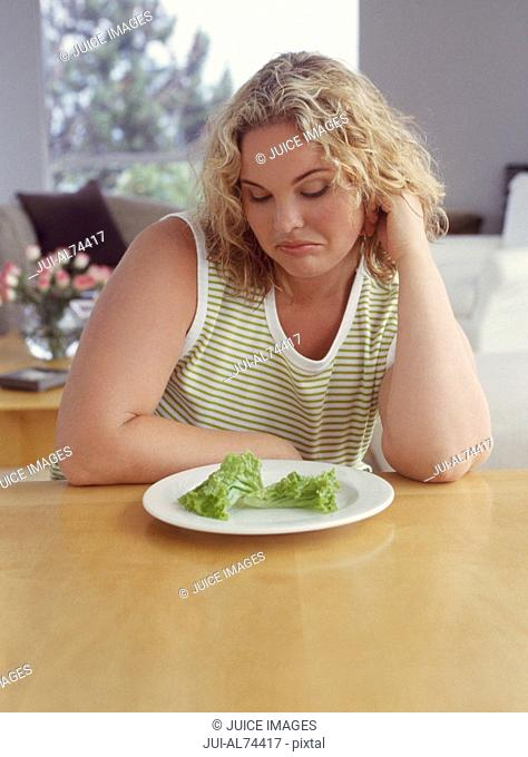 Woman frowning at lettuce