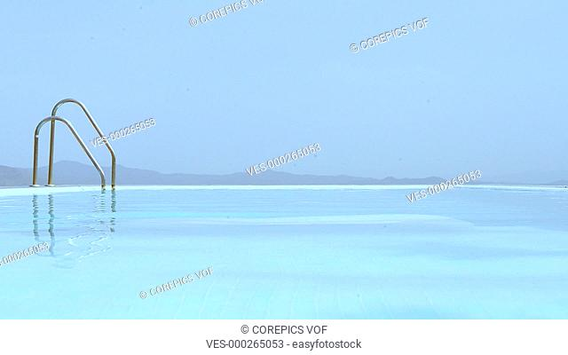 Man, walking from left to right on shallow steps in an infinity pool