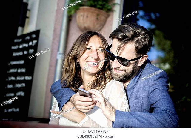 Couple hugging and smiling, using smartphone, Berlin, Germany
