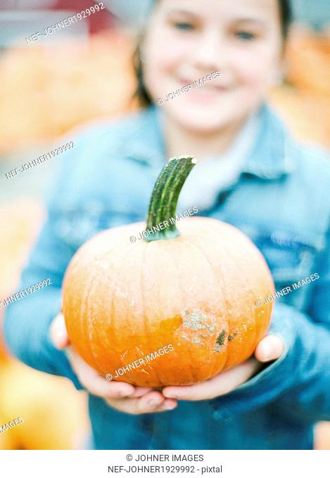 Smiling girl with pumpkin, New Jersey, USA