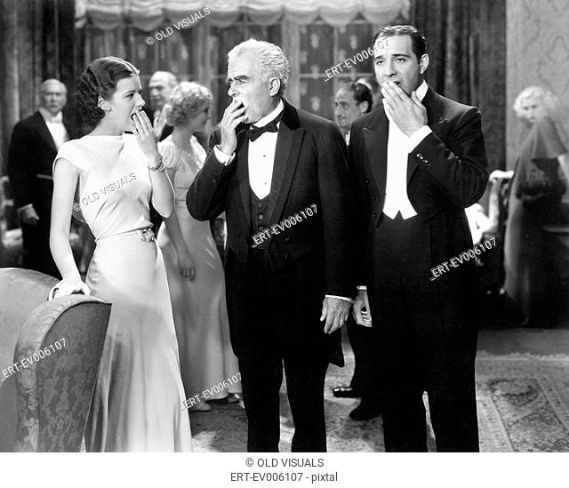 Three people standing together at a formal party yawning and being bored All persons depicted are not longer living and no estate exists Supplier warranties...