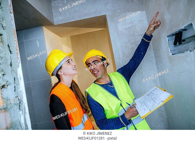Construction worker showing electrical installation to woman