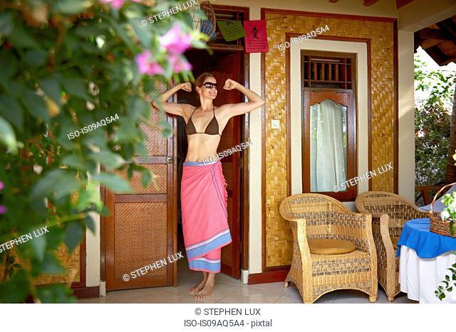 Woman stretching at doorway, Amed, Jemeluk beach, Bali, Indonesia