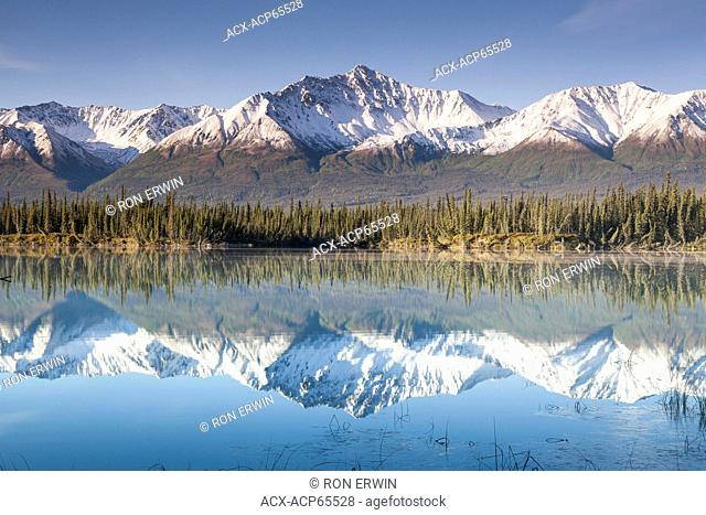 Reflected snow dusted mountains in the Kluane Range of the St. Elias Mountains south of Beaver Creek, Yukon along the Alaska Highway, Canada