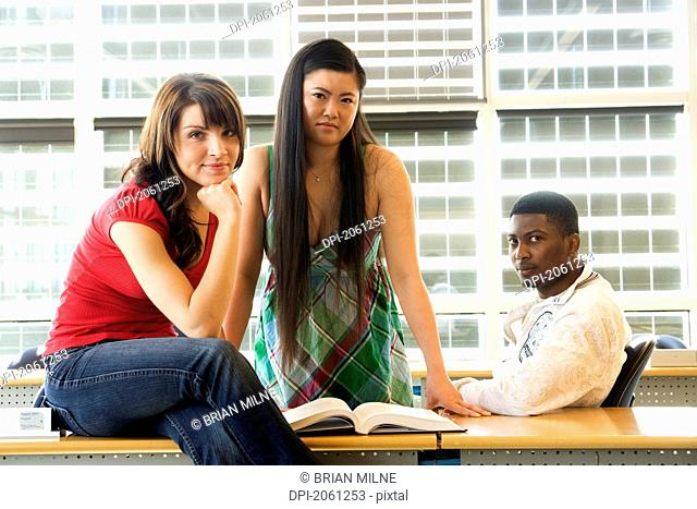 Group Of 3 Students Seated Casually In Classroom, In Front Of Solar Panelled Windows, Winnipeg, Canada