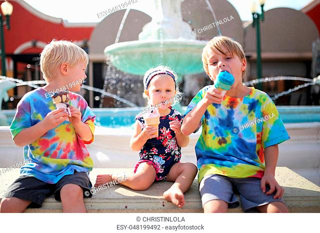Three Young children, including 2 brothers and their baby sister, are sitting outside a restaurant on the patio, eating ice cream cones by a fountain