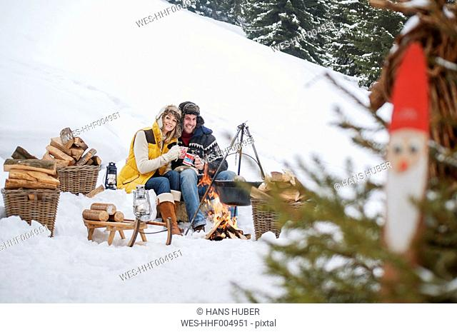 Smiling couple in snow at camp fire