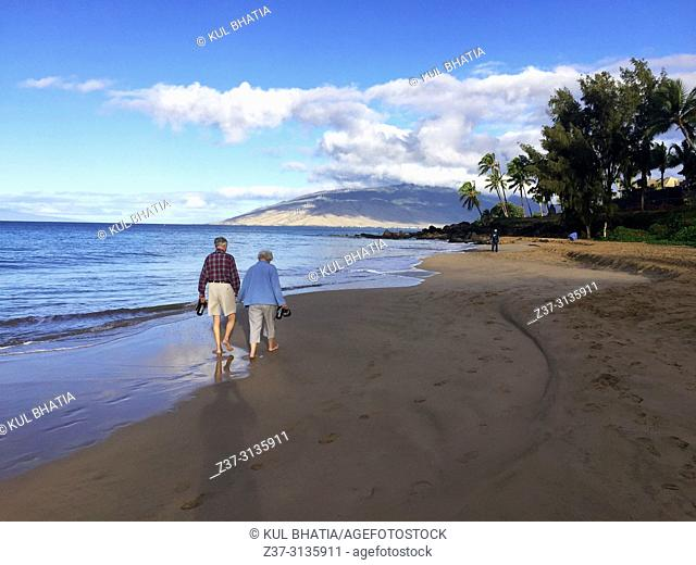 Early morning at the Charley Young Beach, S. Kihei, Maui. An elderly man and woman walk hand in hand, the perfect beginning to a nice day