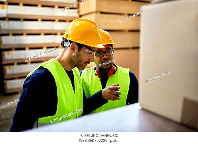 Two workers talking in factory warehouse