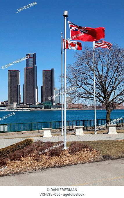 Flags flutter in Riverside Park in Windsor, Ontario, Canada with the General Motors building (Renaissance Center) seen in the distance along the skyline of...