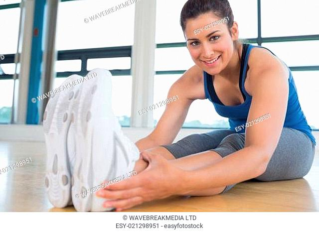 Smiling woman stretching legs in fitness studio