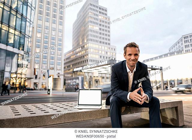 Germany, Berlin, Potsdamer Platz, portrait of businessman sitting on bench with laptop