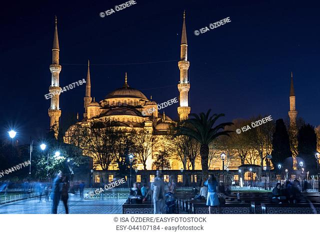 Unidentified people sit in front of Sultanahmet Mosque or Blue Mosque on background in Istanbul,Turkey. 21 April 2018