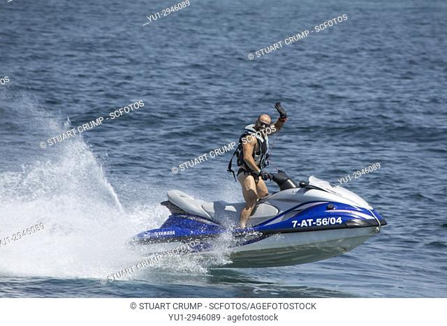 Waiving man on a Jetski in the Mediterranean Sea at Tabarca Spain