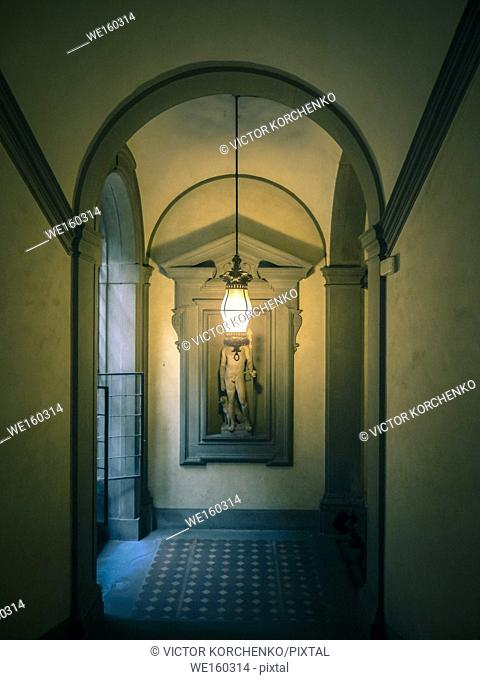 Dark corridor in an Italian palazzo illuminated by a chandelier. Florence, Italy