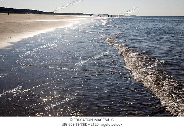 Contre jour waves reaching a sandy beach at Holkham, north Norfolk coast, England
