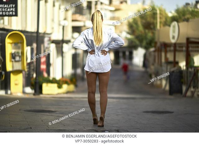 back view of woman without trousers, walking down the road, in summer sun. Russian ethnicity. In holiday destination Hersonissos, Crete, Greece
