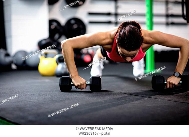 Determined woman doing push ups with dumbbell