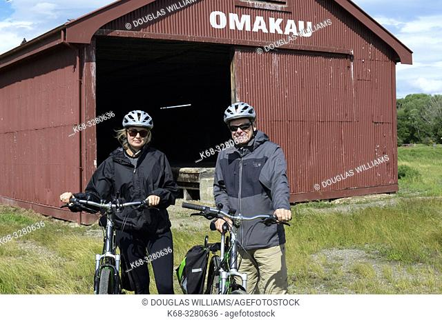 A father and daughter with bicycles on the . Central Otago Rail Trail, Omakau, South Island, New Zealand