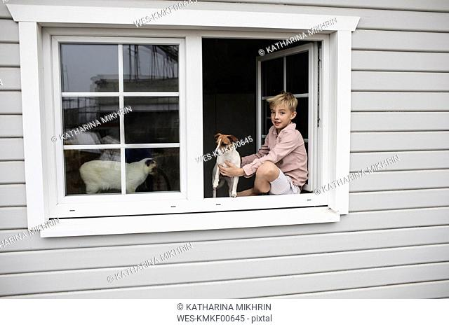 Portrait of boy sitting on window sill with Jack Russel Terrier and Siam cat looking out of open window