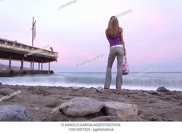 Woman looking into the ocean water's in Yalta, Crimea